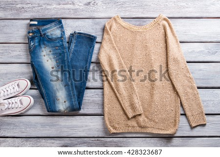 Blue jeans and beige pullover. Sweatshirt on gray wooden background. Spring casual outfit for ladies. Best items in showroom.