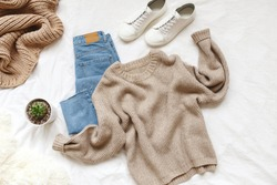 Blue jeans, beige knitted sweater, sneakers, blanket, home plant succulent in a pot lying on bed on white sheet. Overhead view of woman's casual day outfit. Women clothes. Flat lay, top view.