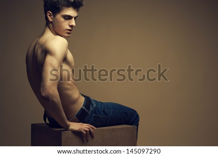 Blue jeans concept. Handsome muscular male model in blue jeans with perfect muscular body posing over wooden background, sitting on a wooden cube. Vogue style. Copy-space. Fashion studio portrait