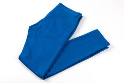 Blue jeans isolated on white background. Folded casual style trousers or pants.