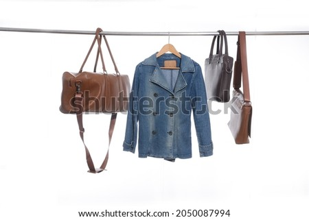 Blue jeans jacket r with three black, brown on hanger  -white background Stock fotó ©