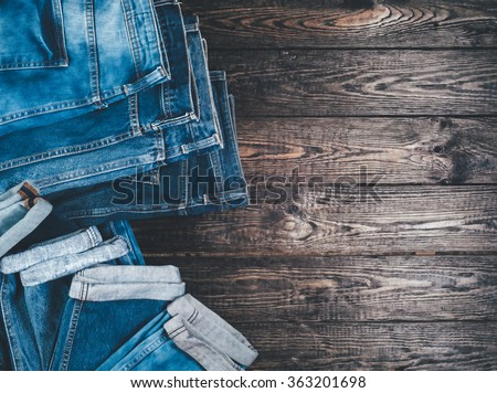 Blue jeans on a brown wooden background.Frayed jeans on a rough wood surface.