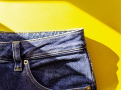 Blue jeans on yellow background with strong shadows.