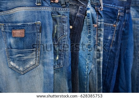 Blue jeans pants clothes pile background. Stack of blue jeans