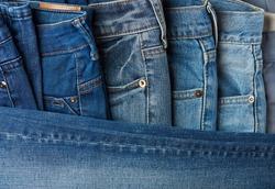 Blue jeans pants clothes pile background. Stack of blue jeans on shop desk