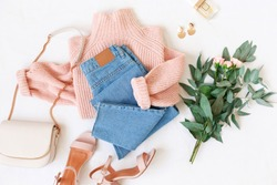 Blue jeans, pink knitted sweater, heeled sandals, small bag and bouquet of flowers lie on white background. Overhead view of woman's casual outfit. Trendy stylish women clothes. Flat lay, top view.