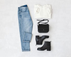 Blue jeans, white knitted sweater, small black cross body bag and leather ankle boots on grey background. Overhead view of woman's casual day outfits. Trendy hipster look. Flat lay.
