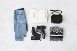 Blue jeans, white knitted sweater, small black cross body bag, leather ankle boots and striped scarf on grey background. Overhead view of woman's casual day outfits. Trendy hipster look. Flat lay.