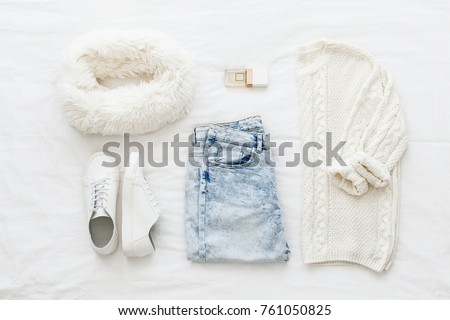 Blue jeans, white knitted sweater, sneakers, fur scarf, perfume lying on bed on white sheet. Overhead view of woman
