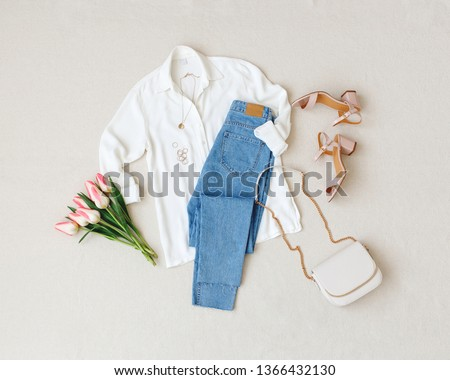 Blue jeans, white shirt, heeled sandals, bag with chain strap, jewelry, bouquet of pink tulips flowers on beige background. Women's stylish spring summer outfit. Trendy clothes. Flat lay, top view.