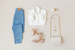Blue jeans, white shirt, pink heeled sandals,  small cross body bag with chain strap, jewelry, accessories on beige background. Women's stylish spring summer outfit. Trendy clothes. Flat lay, top view