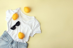 Blue jeans, white shirt, sunglasses and lemons on yellow background. Women's stylish spring summer outfit. Trendy clothes. Flat lay, top view