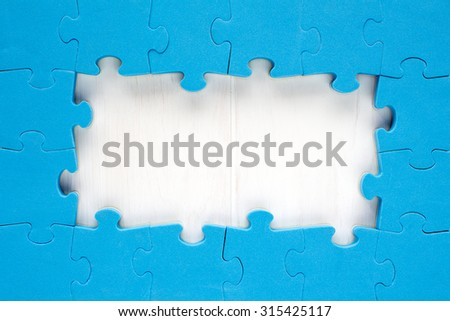 Blue jigsaw puzzle pieces arranged as a border around a wooden surface  with space for your text