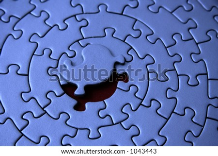 blue jigsaw with the missing piece laying above the space - pieces fitting together in form of a spiral