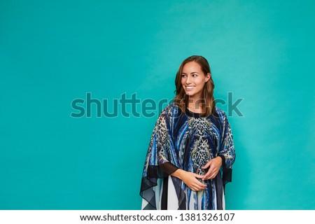 Blue kaftan girl smiling in studio, looking away
