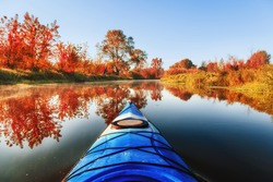 Blue kayak sailing down a river on a sunny autumn day against yellow foliage trees and fog reflected in the water. Exploration of wild pristine nature and wanderlust concept.