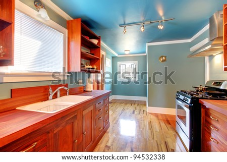 Blue kitchen with cherry cabinets and shiny light floor.