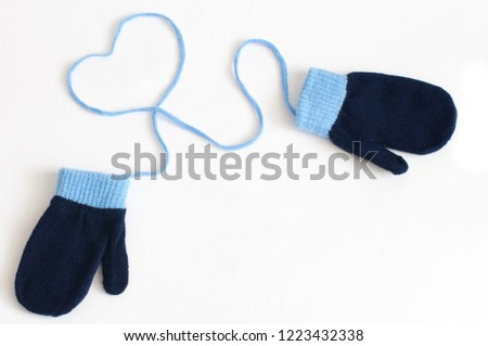 Blue knitted mittens isolated on a white background. Winter symbol. #1223432338