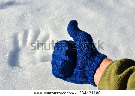Blue knitted wool mitten, thumb up, on a background of white snow with a fingerprint. The concept of the onset of winter or spring, cold or warm #1334621180