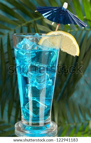 Blue Lagoon cocktail on  tropical background