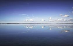 Blue lagoon landscape. Orbetello lagoon with reflection, Argentario, Tuscany, Italy.