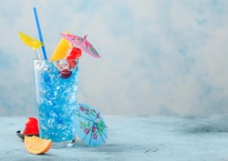 Blue lagoon summer cocktail in highball glass with sweet cocktail cherries and orange slice with umbrella on blue table background. Space for text