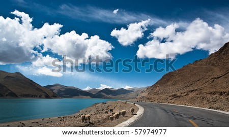 Blue lake with surrounding mountains in great tibet area - stock photo
