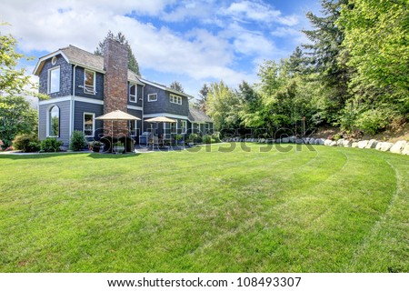 Blue large house exterior with backyard and green landscape.