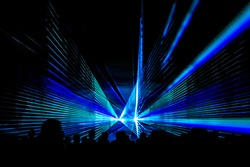 Blue laser show nightlife club stage with party people crowd. Luxury entertainment with audience silhouettes in nightclub event, festival or New Year's Eve. Beams and rays shining colorful lights
