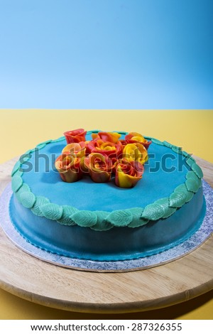 Blue layer cake on a serving plate with edible roses