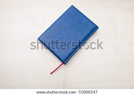 Blue leather diary book laying on wooden table