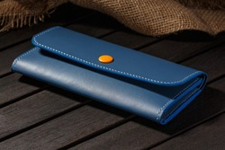 Blue Leather Long Wallet Lies on a Dark Wooden Table