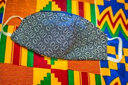 Blue Lesotho pattern corona virus fabric mask laying on red, yellow and green Ghanaian African printed fabric