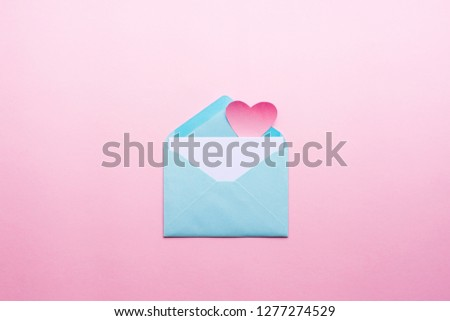 Blue letter with pink heart cartoon style from paper on cardboard background. Valentine day minimal concept Flat lay Top view #1277274529