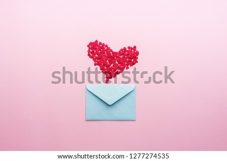 Blue letter with pink heart cartoon style from paper on cardboard background. Valentine day minimal concept Flat lay Top view #1277274535