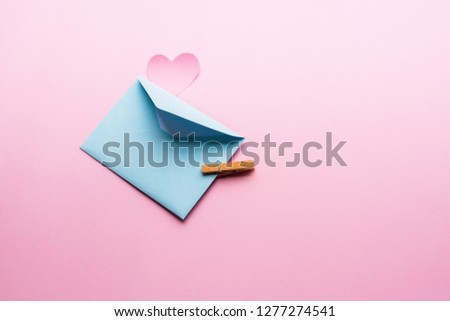 Blue letter with pink heart cartoon style from paper on cardboard background. Valentine day minimal concept Flat lay Top view #1277274541