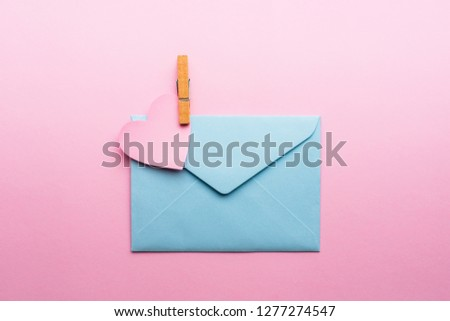 Blue letter with pink heart cartoon style from paper on cardboard background. Valentine day minimal concept Flat lay Top view #1277274547