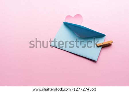 Blue letter with pink heart cartoon style from paper on cardboard background. Valentine day minimal concept Flat lay Top view #1277274553