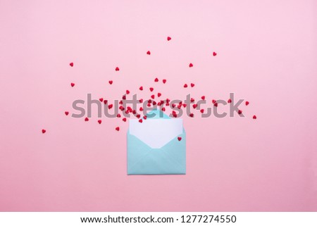 Blue letter with red spreading hearts cartoon style from paper on cardboard background. Valentine day minimal concept Flat lay Top view #1277274550
