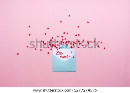Blue letter with red spreading hearts cartoon style from paper on cardboard background. Valentine day minimal concept Flat lay Top view #1277274595