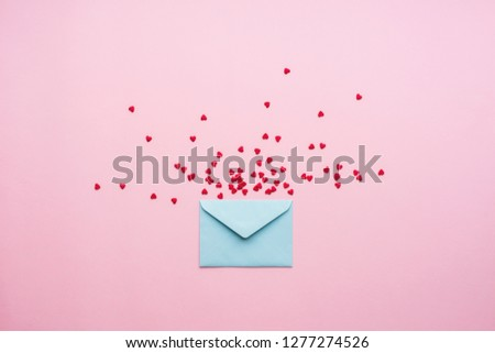 Blue letter with red spreading small hearts Cartoon style cardboard background. Valentine day minimal concept Flat lay Top view #1277274526