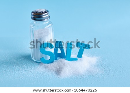 Blue letters spelling the word 'salt' and salt shaker on blue background - Shutterstock ID 1064470226