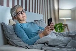 Blue Light Affecting Sleep. Sleepless mature woman suffering from insomnia lying in bed, surfing internet and texting friends via social networks with smartphone,