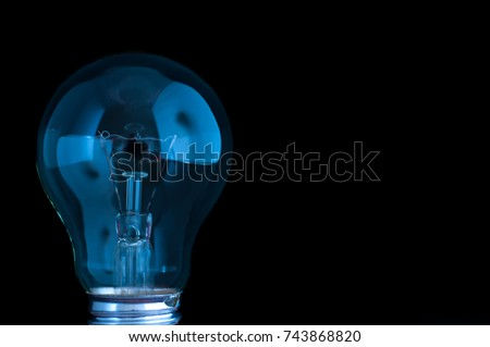 Blue light bulb isolated on black.