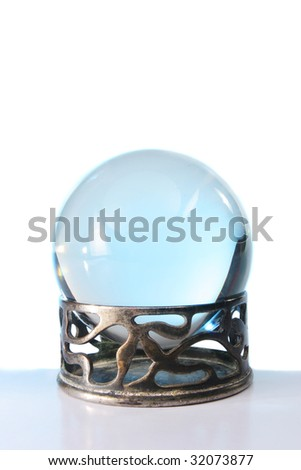 Blue light in a crystal ball in stand against a white background