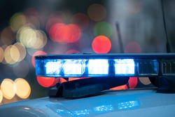 Blue lights on the roof of a police car with the background out of focus and lights with bokeh effect
