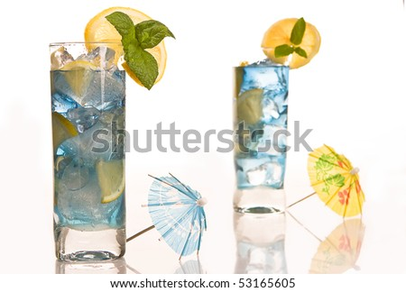 Blue long drink cocktails decorated with lemon and mint