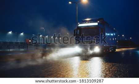 Blue Long Haul Semi-Truck with Cargo Trailer Full of Goods Travels At Night on the Freeway Road, Driving Across Continent Through Rain, Fog, Snow. Industrial Warehouses Area. Сток-фото ©