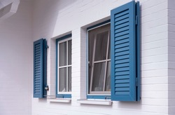 blue louvered window shutters on a white house