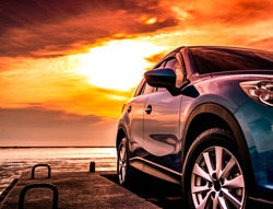 Blue luxury SUV car parked on concrete road by sea beach with beautiful red sunset sky. Summer vacation at tropical beach. Road trip. Front view sports and modern design SUV car. Summer travel by car.